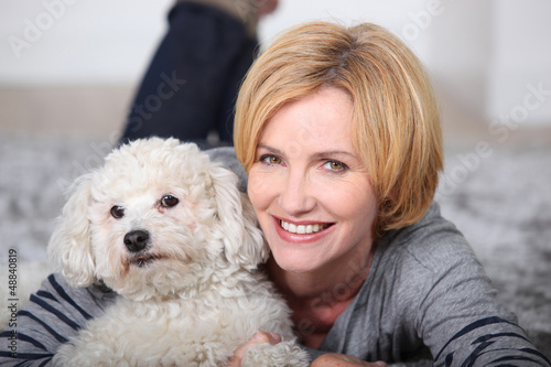 Woman lying on rug with poodle