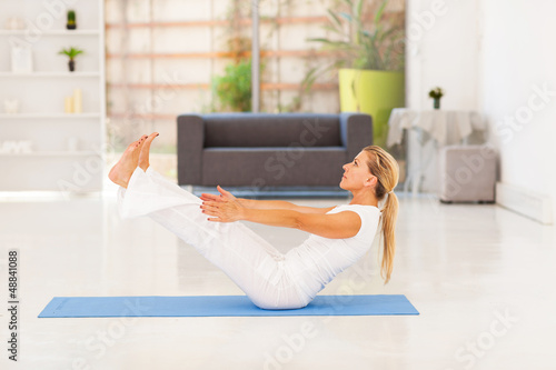 mid age woman doing yoga exercise at home