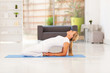 mid aged woman doing yoga at home