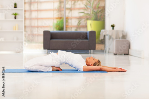 mature lady doing yoga at home