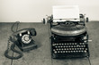 Vintage telephone, old typewriter on wooden table