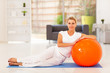elegant middle aged sitting on mat with exercise ball