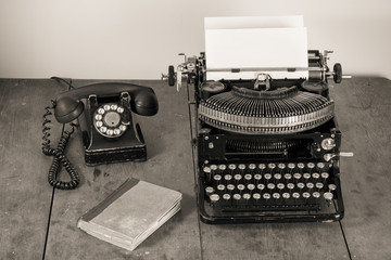 Vintage (1940th) old typewriter, phone, book on table