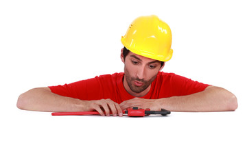 Plumber looking at his tool surprisingly