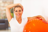 healthy middle aged woman holding exercise ball