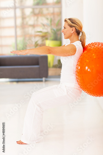 fit middle aged woman workout with exercise ball