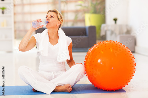 fit mature woman drinking water after exercise at home