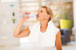 fitness mature woman drinking water after exercise
