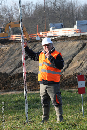 Man on construction site holding pole