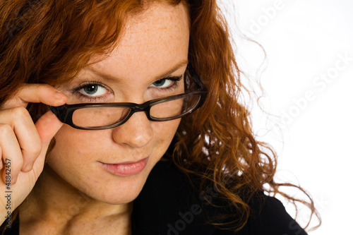Flirting woman looking over her glasses