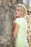 Blond woman stood by stone wall