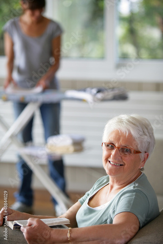 enior woman smiling and a young woman folding laundry