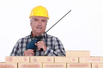 Senior mason holding brick drill
