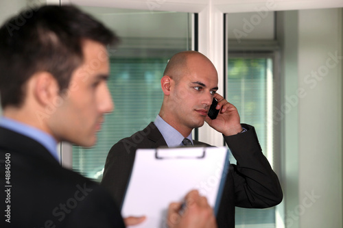 Businessman holding a clip-board whilst colleague call