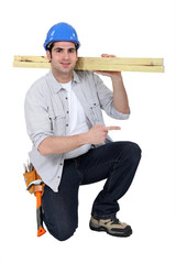 Builder carrying wood on shoulder