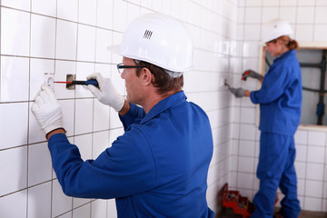 Two electricians working in public rest room