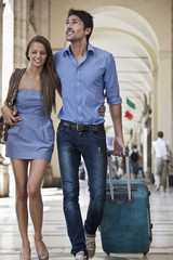 Caucasian couple pulling luggage in city