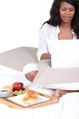 Woman enjoying breakfast in bed
