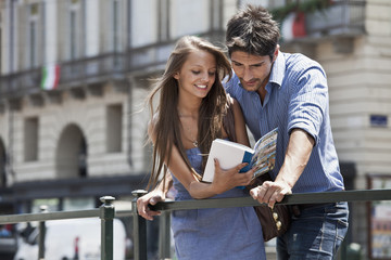 Caucasian couple looking at travel book