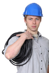 Portrait of electrician carrying coil of wire