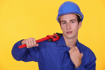 Young worker with wrench in the shoulder