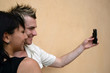 couple taking picture of themselves with cell phone