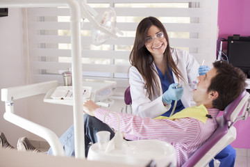 Beautiful female dentist working on a patient