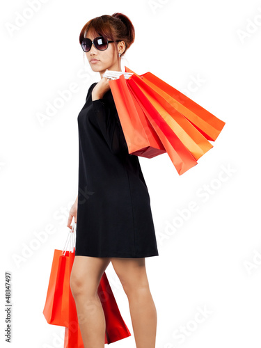 Isolated young asian woman carries shopping bags