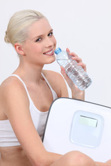 woman drinking bottled water and holding electronic scales