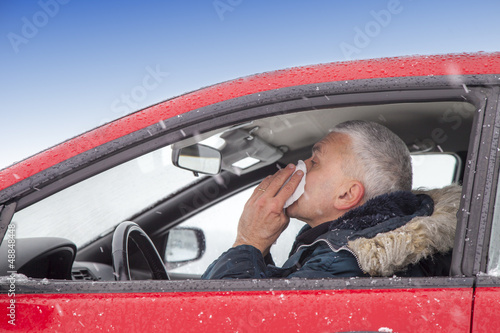 Mid aged man with flu symptoms sneezes in a car