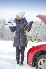 Cute girl waiting for help on the road holding HILFE sign