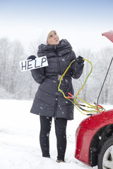 Cute girl waiting for help on the road holding HELP sign
