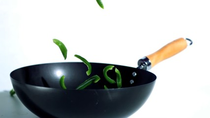 Sliced green peppers falling into wok