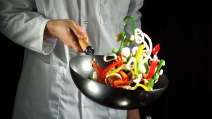 Chef tossing vegetable stir fry in wok