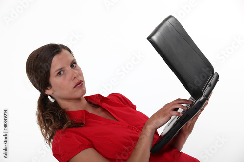 Stern businesswoman holding laptop