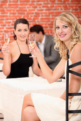 Two female friends drinking champagne in restaurant