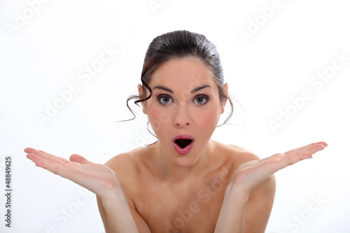 young naked woman looking surprised