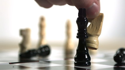 Hand using white knight to knock over king in chess