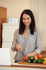 Brunette chopping vegetables in the kitchen