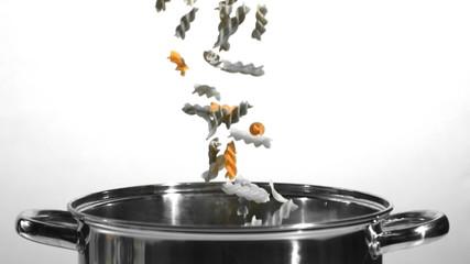 Tricolour fusilli falling into a saucepan