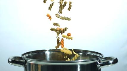 Fusilli falling into a saucepan in black and white