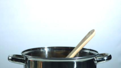 Wooden spoon falling into a saucepan