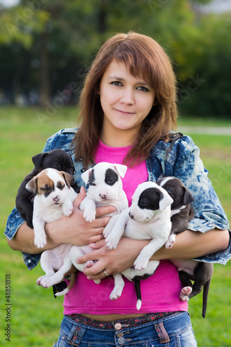 Young Women Holding Five Small Puppies