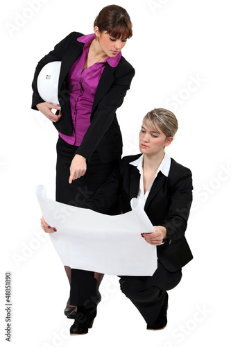 two businesswomen looking at a blueprint