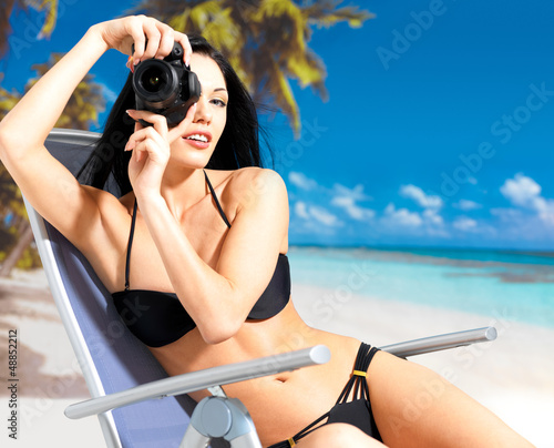 woman with a camera taking photos on beach