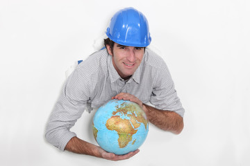 A construction worker holding a globe.