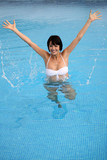 Brunette jumping in swimming pool