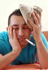 Hombre con dolor de cabeza sujetando una bolsa fría.