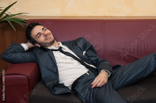 Young businessman relaxing on sofa.