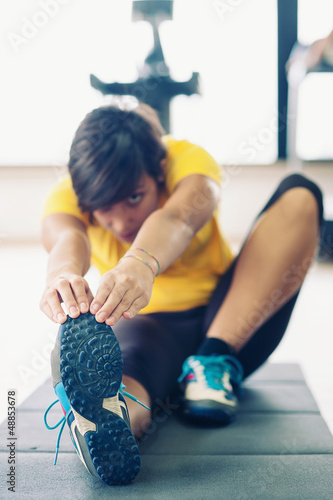 Young woman stretching her leg to warm up in the gym.